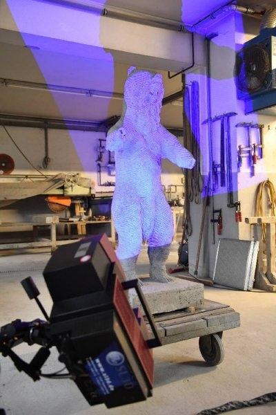 Während auf der Oberfläche des Berliner Bären Messmarken befestigt waren, wurde die in blaues Licht gehüllte Skulptur mit einer Speziallinse Millimeter für Millimeter abgetastet. Foto: Arnold
